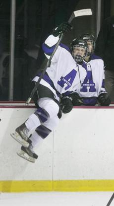The center for Amherst College climbed over the boards during a game.
