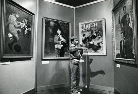 November 15, 1976: Eddie Moczo, 12, of Boy Scout Troop 452 in Jamaica Plain, practiced his his new yo-yo, while eating a lollipop at the Norman Rockwell Boy Scout exhibit at the Shawmut Bank of Boston. Rockwell began his association with the Boy Scouts in 1911 when he was hired to do more than 100 illustrations for the Boy Scout Handbook.