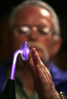 "Mark Vess demonstrates a ""Master Violet Ray"" Quack Medical Coil which emits a series of small electrical shocks purportedly for treating anything from headaches, stomachaches, and muscle pain to more serious diseases such as cancer and various infections. Vess started the Museum of Antiquated Technology in his farmhouse many years ago."