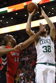 Celtics center Vitor Faverani attempted a fadeaway jumper while being defended by Raptors forward Chuck Hayes in the first quarter.