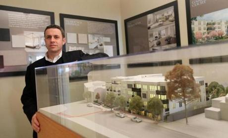 Developer Jordan Warshaw with a model of the Belclare, his 30-unit luxury condo project at the site of the old Wellesley Inn on Washington Street.