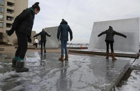 Sarah Bettigole, 13, of Wellesley slides along one of the sculptures that lines the Harbor Walk with her friends with her friends in Boston, Mass