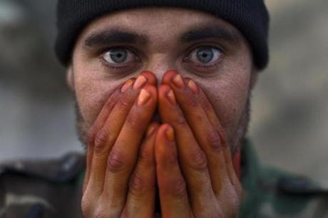"Louie Palu's ""Afghan soldier warming his henna-stained hands on the front lines, Zhari District, Kandahar, Afghanistan."""