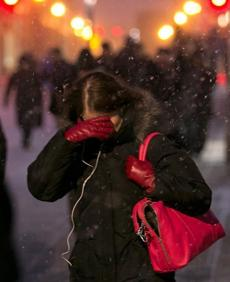 A woman shielded her face walking near North Station.