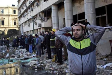 An Egyptian man stood in rubble after an explosion hit the the Egyptian police headquarters in downtown Cairo on Friday.