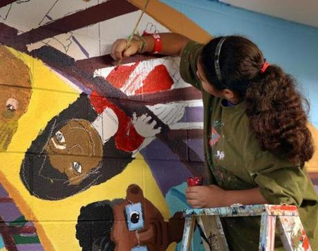 Sixth-grade student Brigitte Alcantara practices her handiwork on a portion of the wall.