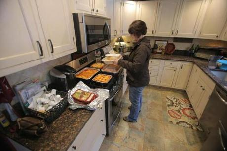 Joanne Stanway prepares containers of lasagna she made.