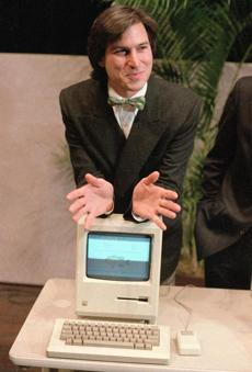 Steve Jobs leaned on the new Macintosh personal computer following a shareholders' meeting in 1984.