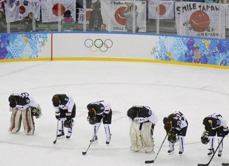 Japan's women's hockey team bows after a 4-0 loss to Germany.