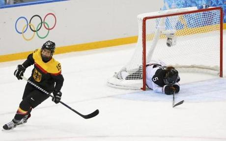 After a German goal, the puck and a Japanese player are both in the net.