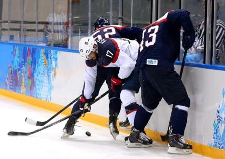 Ryan Kesler of the US is crunched by two Slovaks.