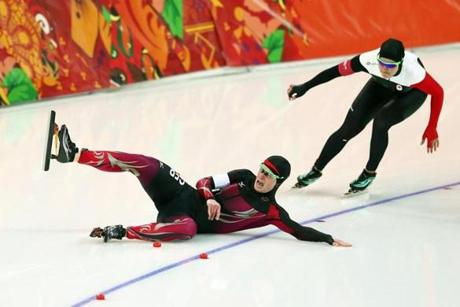 Monique Angermueller of Germany slips in front of Canada's Kaylin Irvine during long-track speedskating.