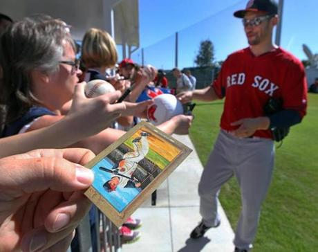 A fan held a baseball card for an autograph from Grady Sizemore from his days with the Cleveland Indians.