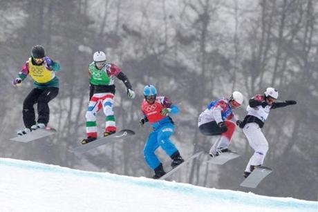 A fleet of boarders soar over a hill in men's snowboardcross.