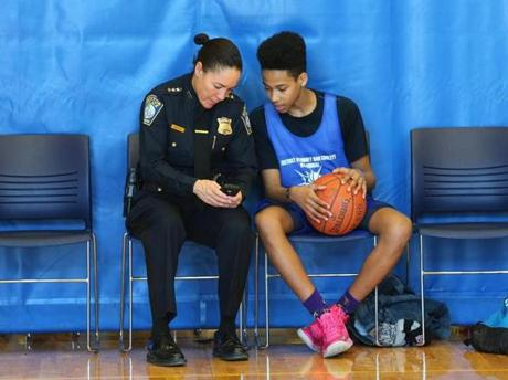 Boston Police Deputy Superintendent Nora Baston spent time with Emanuel Green, 15, of Dorchester as she showed him photos on her smartphone during a break in the action.