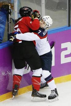 Monique Lamoureux of the US (right) mixes it up along the boards with Canada's Lauriane Rougeau of Canada.