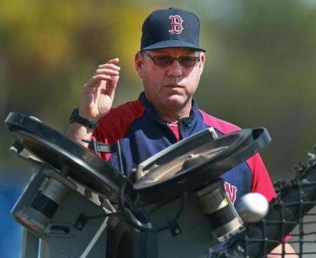 Minor league coach Rich Gedman fed a pitching machine during batting practice.