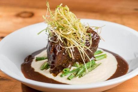 Braised short ribs in a cauliflower puree and served with green beans and fried leeks.