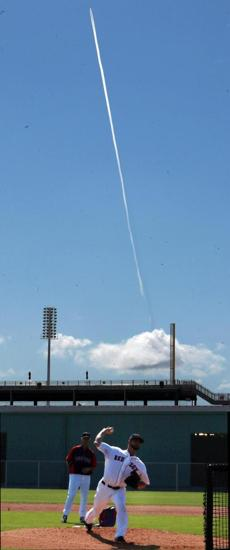 A jet contrail was in the sky over Brandon Workman as he threw live batting practice.