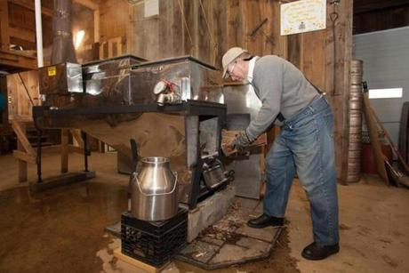 John Koepp adds wood to the burner of a sap boiler at Ioka Valley Farm.
