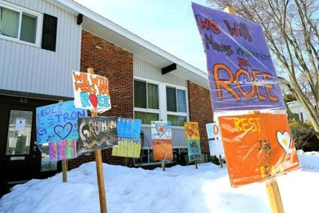 Signs made by children to remember Roee Grutman have been planted in front of the Newton home where he lived.