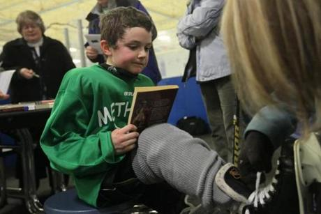 "Feb 27, 2014 - -METHUEN ,MA- SKATE AND READ - Owen Howell (cq), 8, of Methuen, holds on to his book he just checked out ' Indian in the Cupboard"" while his mom Christine pulls of his skates after practicing at the Methuen Fun Hockey League and its Skate & Read program, which combines ice hockey instruction with encouraging school chldren to read more for pleasure. Librarians brought books in to one of the practices so kids getting off the ice have chance to pick one or two from their reading list (globe staff photo :Joanne Rathe section: G reporter: JOSEPH KAHN topic: skateandread )"
