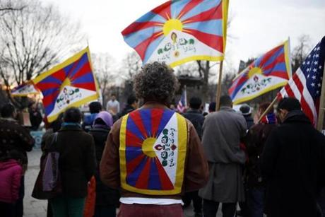 Demonstrators carried and wore Tibetan flags on the Boston Common to protest China's rule over Tibet.