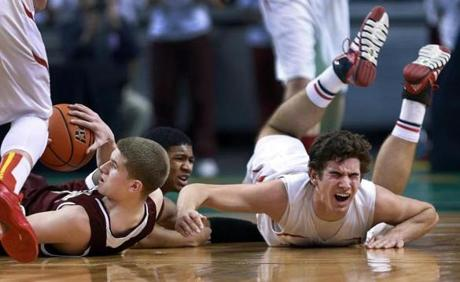 03/10/14: Boston, MA: Bishop Connolly's Jack Santoro (right) grimaces as he hits the floor during a second half loose ball scrum. Saint Clement's Jack Hartnett (left) and Brandon Williams (center) are also involved. Saint Clement met Bishop Connolly in the boy's Division 4 State Semi Final in basketball, the game was held at the TD Garden. (Jim Davis/Globe Staff) section:sports topic:11Gardenhoops