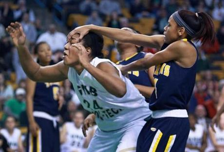 New Mission 's Taneja Drayton (right) fouled Greater New Bedford's Nakira Examond (left) with a palm to the head in the girl's Division 4 State Semi Final in basketball at TD Garden.