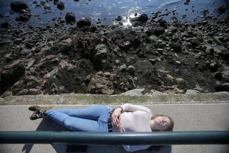 Jessie Nocella, 18, of Peabody, sunbathed above the rocks on the Lynn Shore Reservation as a beautiful day brought people out to enjoy the weather.