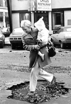 February 11 1970: Mrs. Kevin Murphy of Quincy carried her one year old daughter Heather through this dangerous looking pothole in Park Square.