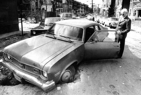 February 26 1977 / fromthearchive / Globe Staff photo by Charles Dixon / John F. Barrett of Dorchester inspected the pothole that swallowed his front tire at the corner of East Cottage street and Dorchester avenue.