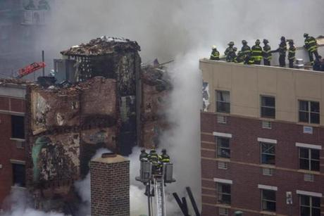 New York City firefighters examined the rubble after a deadly building collapse in Harlem.