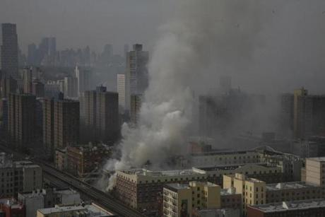 Smoke poured from the site of an explosion and building collapse in East Harlem on Wednesday afternoon.