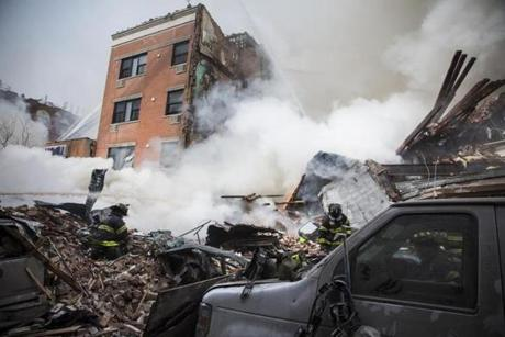 Heavy smoke poured from the debris as the Fire Department of New York responded to a 5-alarm fire and building collapse at Park Ave.