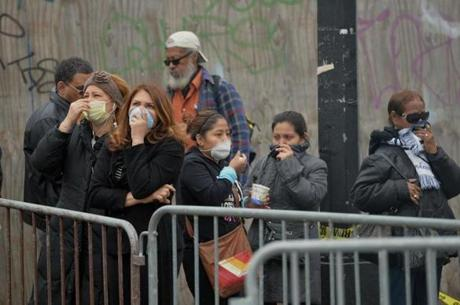 Bystanders covered their faces as  smoke filled the area.