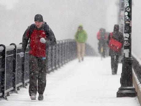 Snow and wind battered pedestrians on the Massachusetts Avenue Bridge in Cambridge Thursday. Earlier in the week, temperatures had neared 60 degrees in the city.