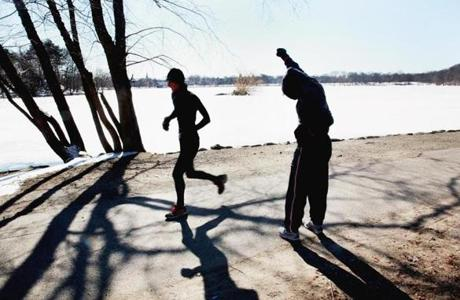 Boston, MA 031414 Ni Vo (cq), right, of Dorchester did warm-up exercises before her run around Jamaica Pond in Boston, Friday, March 14 2014. (Wendy Maeda/Globe Staff) section: Metro slug: 15standalone reporter: In-Cap