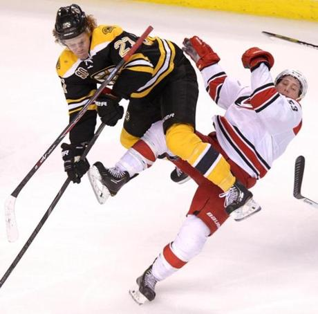 Boston, MA - 03/15/14 - (3rd period) Boston Bruins defenseman Dougie Hamilton (27) lays out Carolina Hurricanes left wing Jeff Skinner (53) with a heavy open ice hit in the third period. The Boston Bruins take on the Carolina Hurricanes at TD Garden. - (Barry Chin/Globe Staff), Section: Sports, Reporter: Amalie Benjamin, Topic: 16Bruins-Hurricanes, LOID: 7.3.1322190722. Boston, MA - 03/15/14 - (3rd period) The Boston Bruins take on the Carolina Hurricanes at TD Garden. - (Barry Chin/Globe Staff), Section: Sports, Reporter: Amalie Benjamin, Topic: 16Bruins-Hurricanes, LOID: 7.3.1322190722.