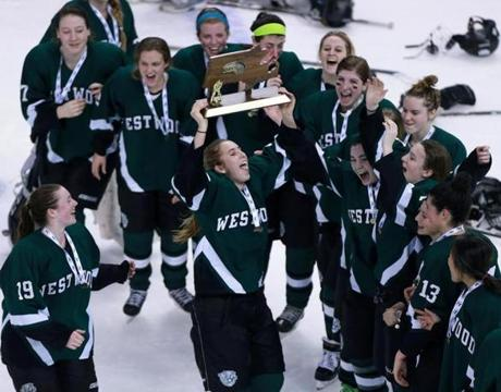 03/16/14: Boston, MA: Westwood's Kim Egizi hoists the trophy as she and her teammates celebrate thier victory. Westwood defeated Wellesley in the Division Two State Championship girl's ice hockey game at the TD Garden. (Jim Davis/Globe Staff) section:sports topic:hockey state finals
