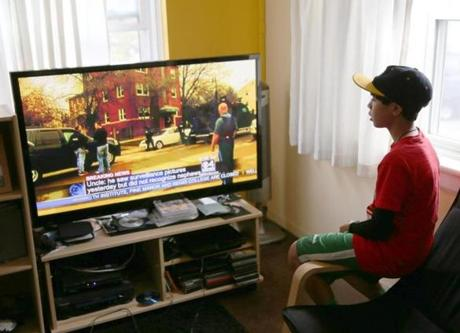 A 12-year-old watches a TV report to see what's happening outside his Watertown apartment.