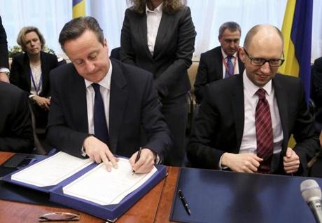 Britain's prime minister, David Cameron, signed a pact with Ukraine's prime minister, Arseniy Yatsenyuk, in Brussels.