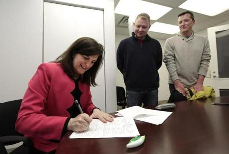 Oakland County Clerk Lisa Brown signed a marriage license for Justin Flowers and Josh Redder in Pontiac. About 300 couples wed Saturday in four Michigan counties before a federal appeals court placed a stay on a federal judge's decision overturning the state's 2004 constitutional ban on same-sex marriage.