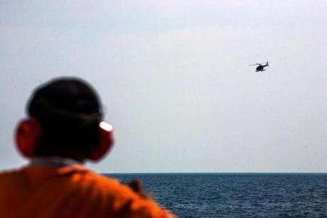 A member of Indonesia's National Search and Rescue operation looked on as a helicopter flew overhead.