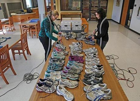 Boston, Ma., 03\24\14, Tiffany Locke, left and Emily Shafer, right clean running shoes left at the Marathon memorial last year. They'll be part of an exhibit on the bombings planned for the Public Library on Boylston Street. Section: Metro Suzanne Kreiter/Globe staff (The Boston Globe)