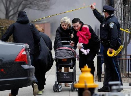 Boston, Massachusetts -- 03/26/2014-- A police officer holds up caution tape as a man and woman holding a baby run away from a nine alarm fire at 298 Beacon Street in Boston, Massachusetts March 26, 2014. Jessica Rinaldi/Globe Staff Topic: 27Fire08