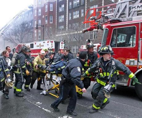 03/26/14: Boston, MA: A nine alarm fire broke out this afternoon at 298 Beacon Street. Frantic fire fighters scream for an ambulance as they work on and rush an injured fire fighter on a stretcher down Beacon Street. (Jim Davis/Globe Staff) section: metro topic:27fire(3)