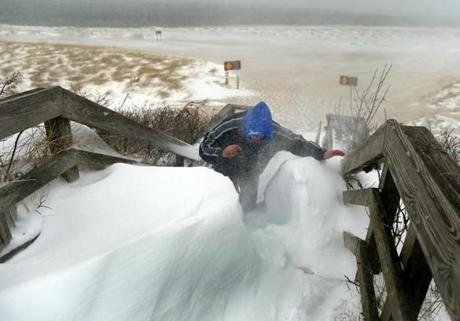Chatham-03/26/14-It was blizzard conditions as snow blowed sideways through Chatham with winds approaching 50mph. Mark Sudduth(cq) from North Carolina struggles to get through a snowdrift on the stairs leading to Chatham Lighthouse Beach. where he shot some video. Boston Globe staff photo by John Tlumacki (metro)