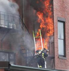 A firefighter held onto a ladder as flames erupted from a third-floor window.