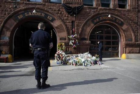 Boston, Massachusetts -- 03/27/2014-- People pause to pay their respects at a makeshift memorial outside of the Firehouse on Boylston Street following yesterday's nine alarm fire at 298 Beacon Street that killed two Boston firefighters in Boston, Massachusetts March 26, 2014. Jessica Rinaldi/Globe Staff Topic: 28Fireaftermath11